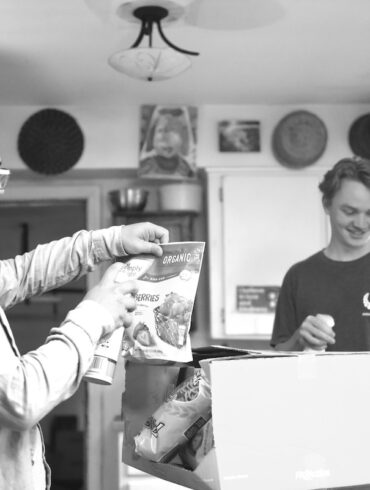 Image of two young men sanitizing groceries at a kitchen table