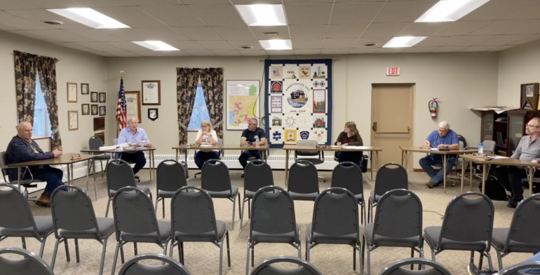 Seven Garrettsville village sit maskless at tables in front of several empty chairs
