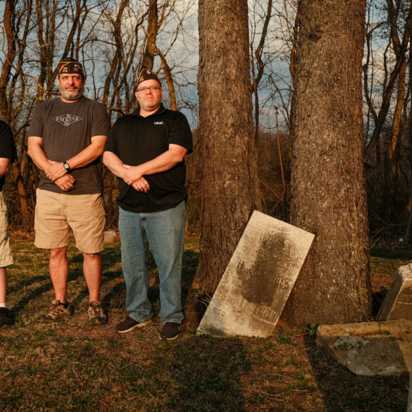 Image of three men standing next to old grave stones