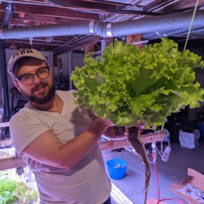 Image of man holding a giant head of lettuce