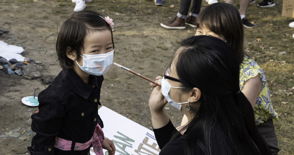 Image of a woman painting the surgical mask of a toddler