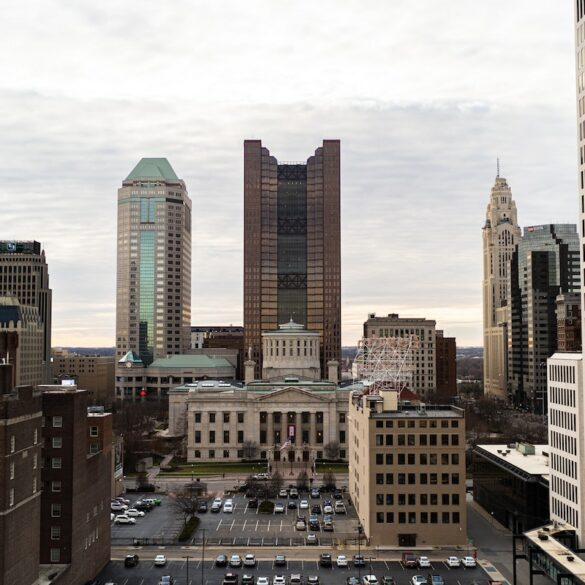 Image of the Ohio statehouse from a distance, surrounded by skyscrapers