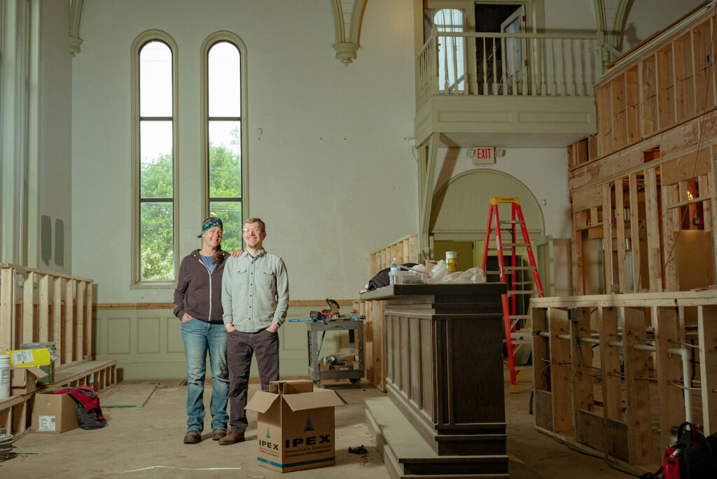 Image of a white man and woman standing in a large chapel-like space. There is a dark bar top to there left and the space is under construction.