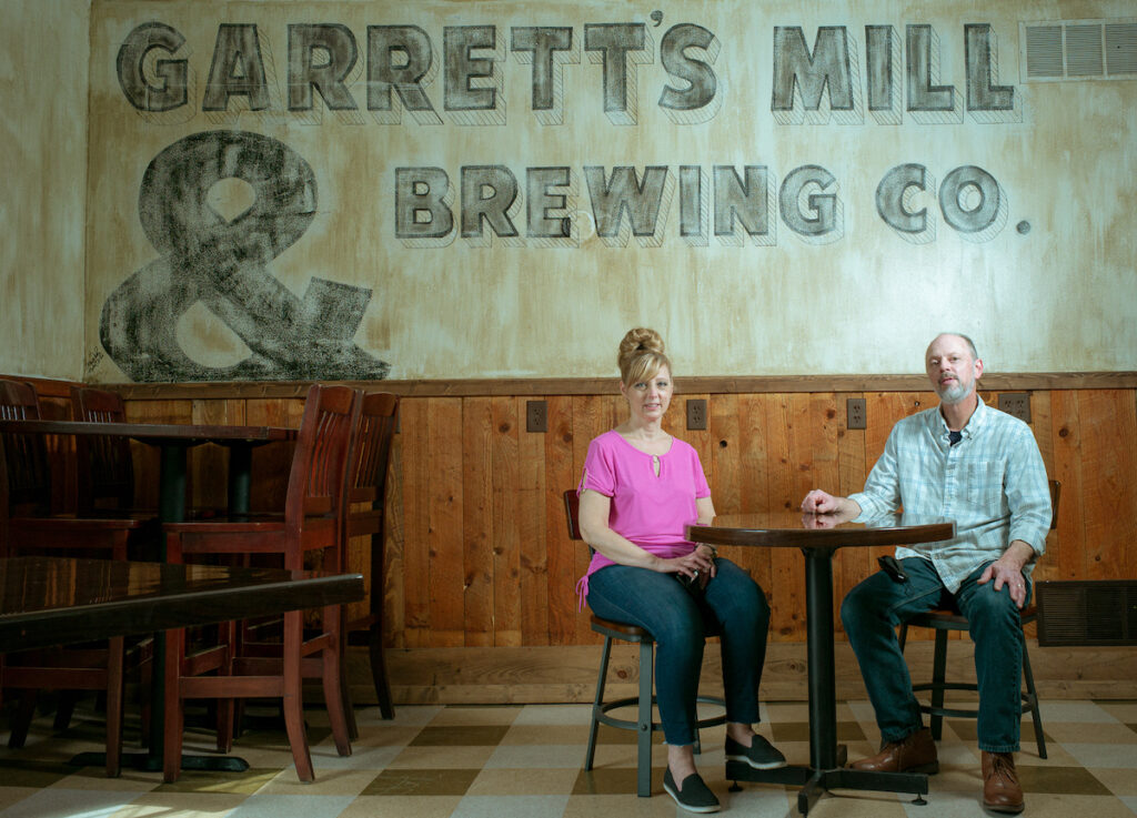 """Image of a white man and woman sitting at a table in front of a wall mural that reads """"Garretts Mill and Brewing Co."""