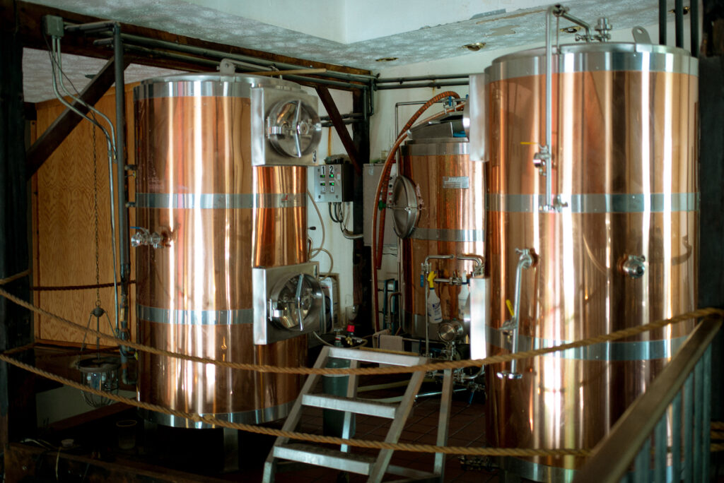 Image of three large copper vats used for brewing beer