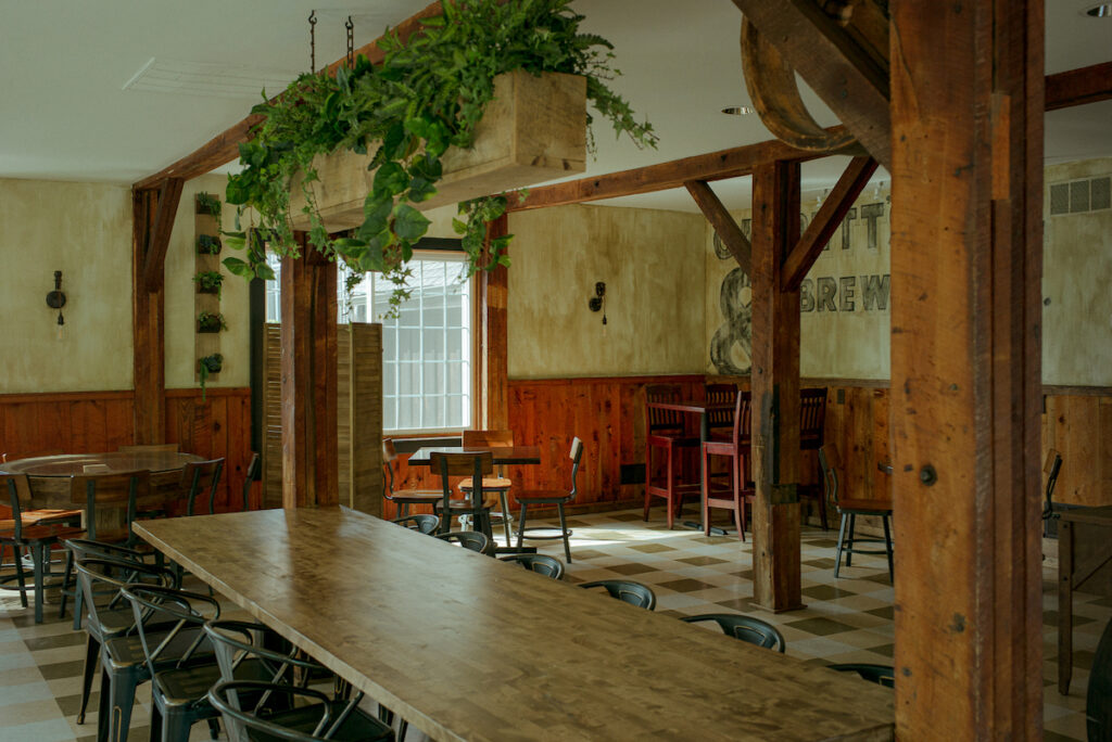 Photo of a cozy dining area with exposed wood beams and thick wooden tables and green plants hanging down stylishly aged walls.