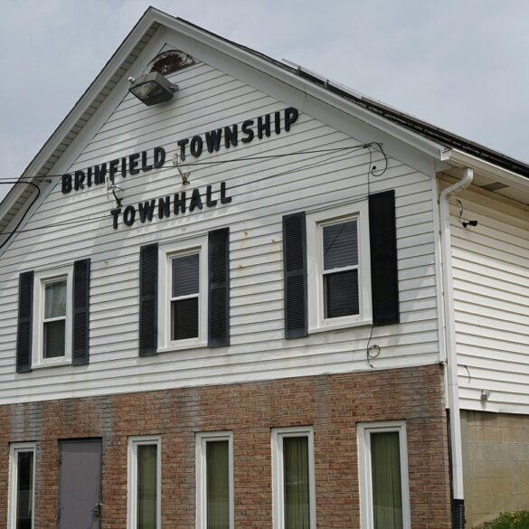 image of the brimfield town hall, a white siding and brick building, on a cloudy day