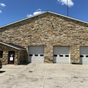 Image of Rivers Garage and Body Shop, a stone front building with three white garage doors