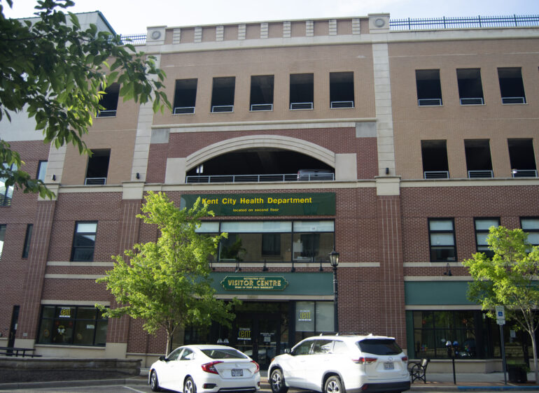 image of the front of a brick building with a green sign indicating the Kent City Health Department