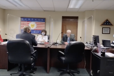 image of four county commissioners and finance directer sitting around a wooden desk, separated from each other by plexiglass