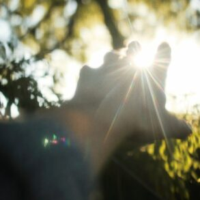 image of a hand reaching toward the sun and disappearing into a lens flare.