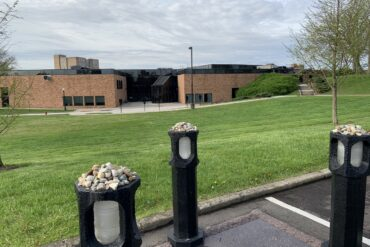 Image of the May 4 memorial, four posts in a parking space, in front of the Gym Annex