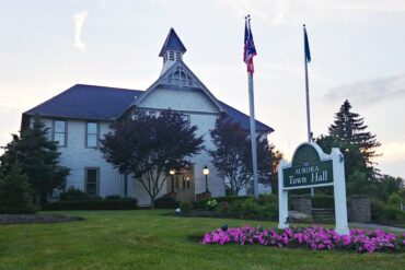 Photo of the front of aurora's town hall building with bright purple flowers around the sign in the front lawn.