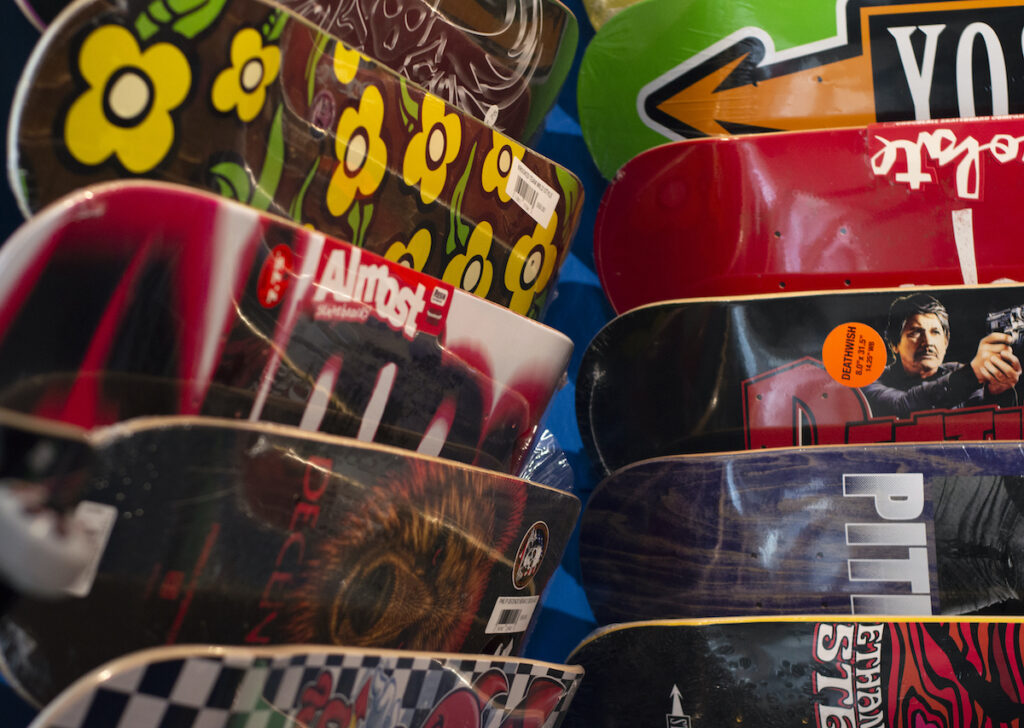 Photo of a wall of hanging skateboards. The boards are overlapping and cover the entire wall with vibrant colors and skate crew-type art.