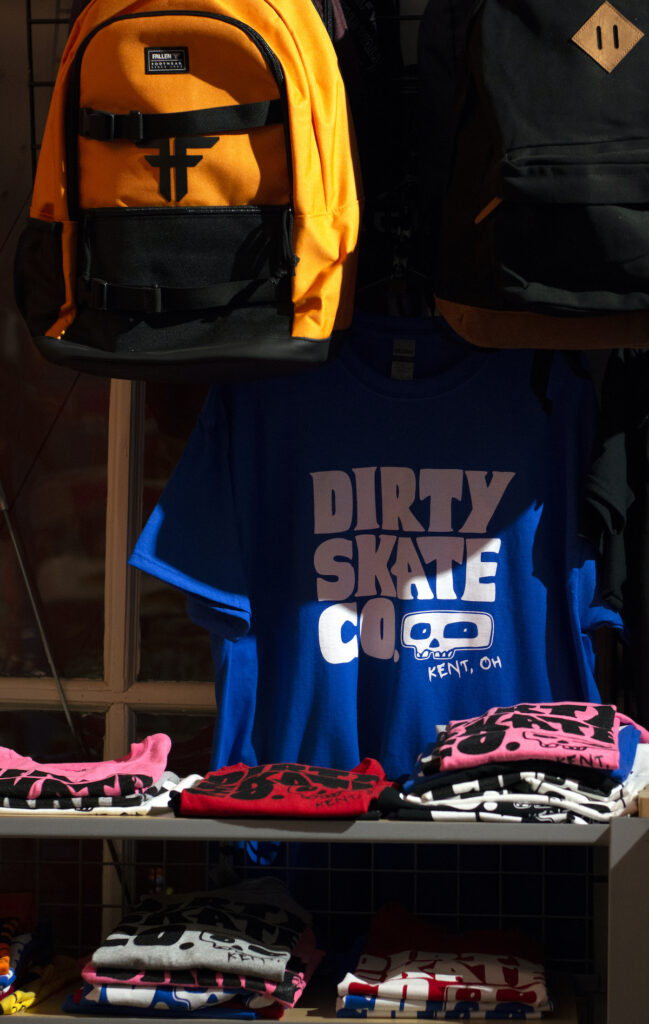 """Photo of a shop display with folded t-shirts and a yellow backpack hanging up. One shirt is hanging prominently behind the shelf. It is a vibrant blue and says """"dirty skate co."""" in white lettering with a cartoon drawing of a skull, also in white."""