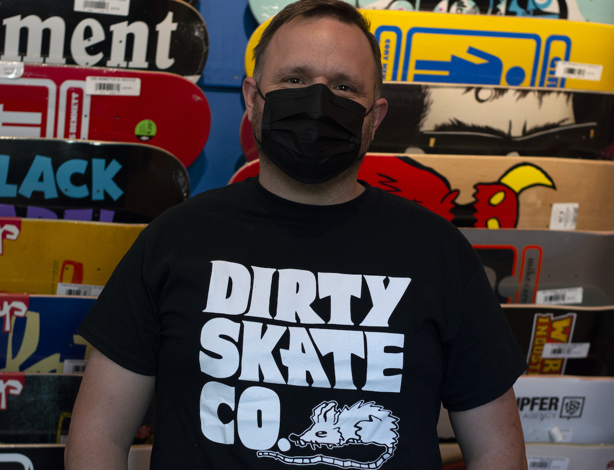 """Headshot of a white man standing in front of a wall of colorful skateboards. His is wearing a black medical mask and a black t-shirt that says """"Dirty Skate Co. with a drawing of a scruffy rat."""