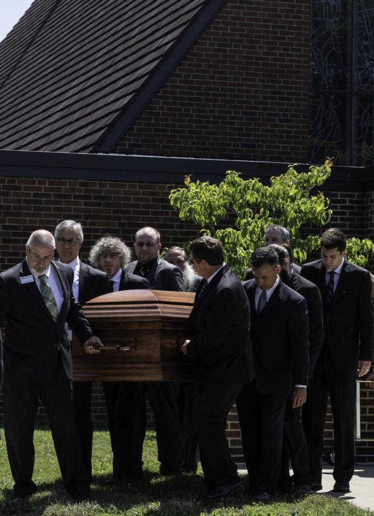 Photo of ten pallbearers carrying roger di paolo's casket.