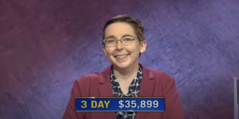 """Screenshot of a headshot of Katie Sekelsky on the Jeopardy set. She is smiling at the camera and a graphic on the screen reads """"3 day $35,899"""""""