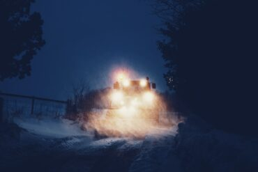 Image of a snowplow at night on a winter road