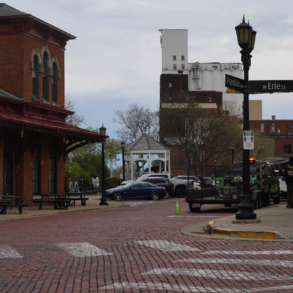 Photo of a red brick road intersection in downtown Kent. The street signs on the corner read franklin ave and Erie Street