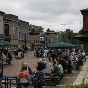 image of franklin avenue, a red brick street with long picnic tables scattered down the street. People are sitting at the tables enjoying drinks and chatting. The sky is overcast.