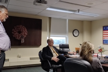 Image of a man standing and speaking to Portage County commissioners in the Board of County Commissioners meeting room