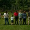 Image of a foster family in a grassy yard, with their backs to the camera for privacy
