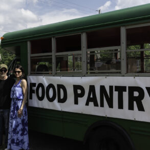 Image of two people standing in front of a green schoolbus with the words Food Pantry on the side