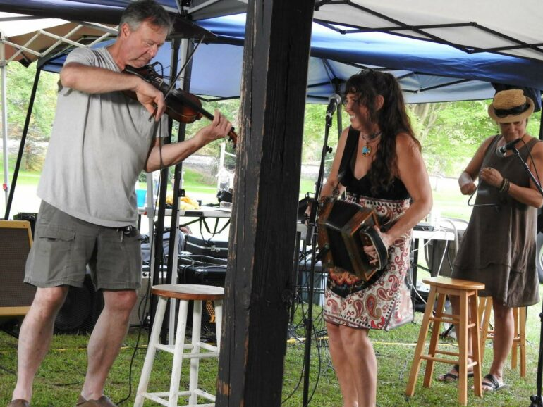 Image of a man playing the fiddle and a woman playing an accordian outdoors