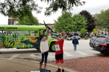 Image of two men in front of a large green bus in downtown Kent