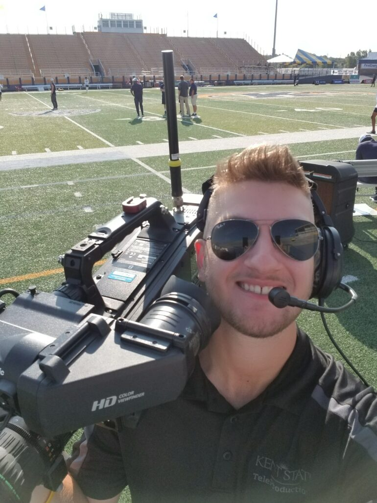 Selfie of a young white man with combed light hair and aviator sunglasses holding a huge video camera on his shoulder and a headset with a microphone. He's standing on the sidelines of a football field.