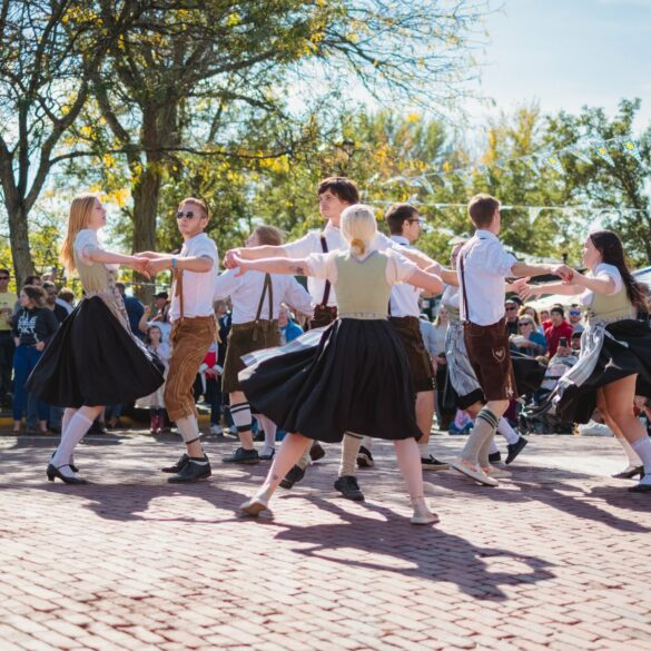 Photo of a group of teenaged dancers in german folk costume, spinning on a brick street.