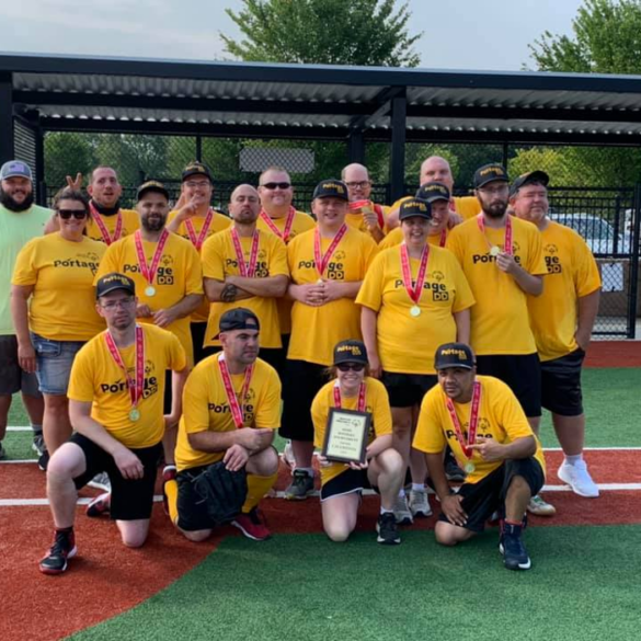 Photo of a softball team posed in front of the dugout with one row kneeling, and two rows standing. The people are wearing bright yellow Portage DD t-shirts and black Portage DD baseball caps. A person in the front row is holding a plaque and the whole team has gold medals with red ribbons around their necks.
