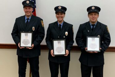Three young people pose for a photo holding up certificates, wearing formal firefighters' uniforms.