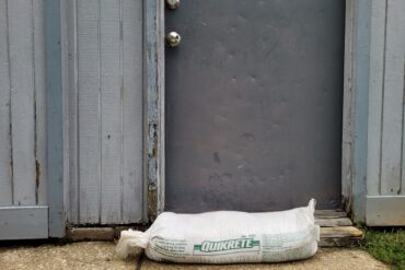 An image of a small sandbag in from of an apartment door