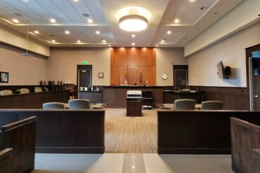 Photo of the inside of a court room, from the back of the room and looking toward the judge's desk
