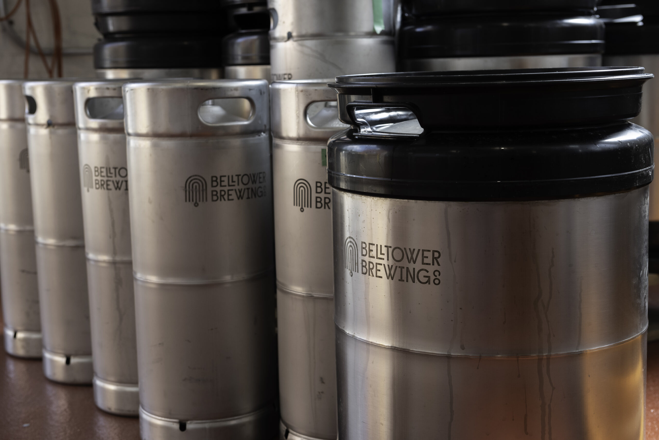 photo of several large stainless steel drums with Bell Tower Brewing Co. written on the side in black lettering