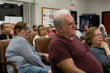 Image of residents seated in a local fire station watching a meeting