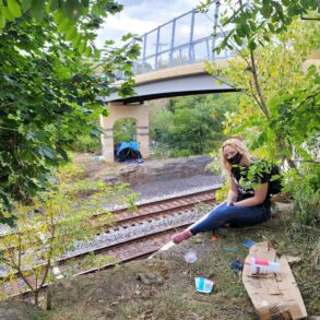 Image of a woman in jeans and a T-shirt near the railroad tracks in Kent under the Haymaker bridge